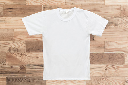 White blank T-shirt on wood texture background photo