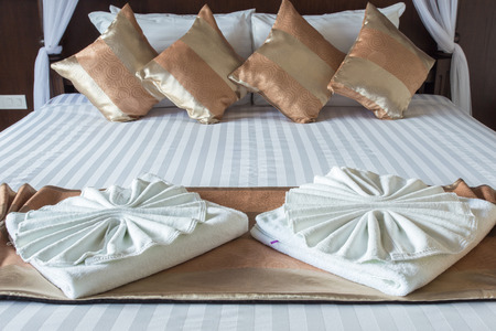 Close up of nice towels on white bed sheet with golden pillow photo