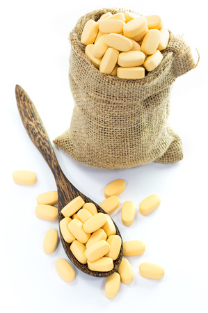 Yellow pills in Empty burlap sack and on spoon isolated on white background photo