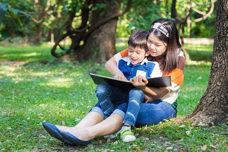 母亲与她的儿子读一本书在树下的公园