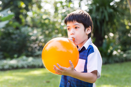 Little boy blowing a orange balloon in park on a sunny day.
