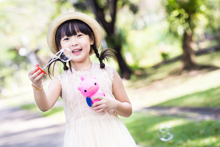 Asian little girl is blowing a soap bubbles with smile face in park photo