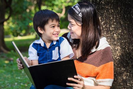 mama e hijo: Madre leyendo un libro con su hijo con cara de sonrisa en el parque bajo el árbol