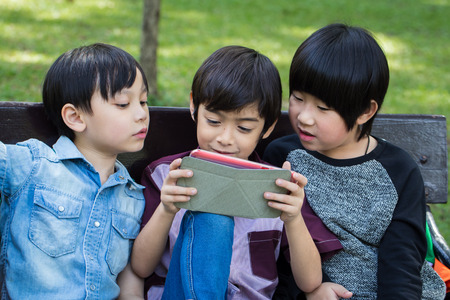 Three Little handsome boy looking on tablet and playing game at park