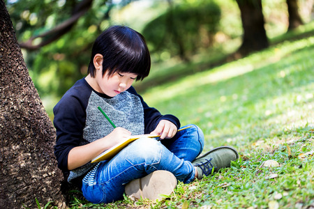 Little asian boy writing book with pencil in the park Standard-Bild