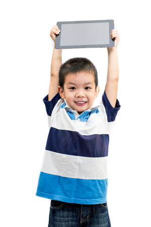 Little handsome boy portrait holding tablet with smiling face isolated on white background photo
