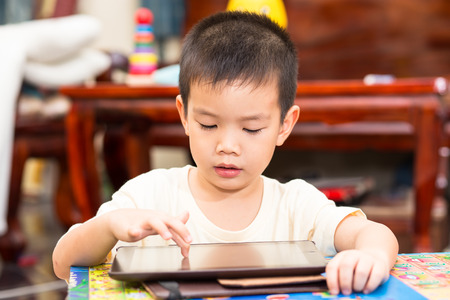 Little handsome boy touch on tablet and playing game at home
