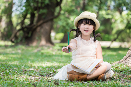 Little asian girl show pencil for writing book with smiling face in the park Stock Photo