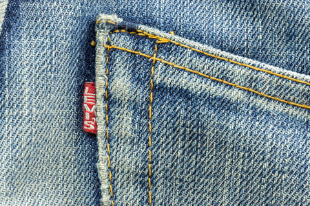 levi: BANGKOK, THAILAND - March 24, 2014: Closeup of Levis pocket and Levi tag label of logo sewed on a blue jeans isolated on white background.Levi Strauss & Co is a privately held American clothing company.
