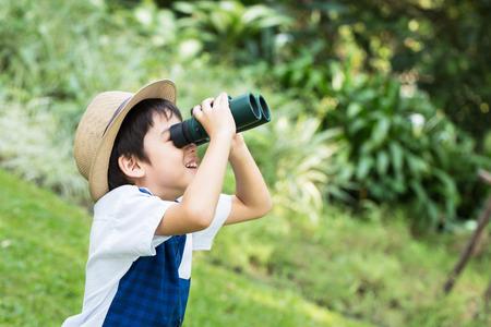 작은 아시아 소년 공원에서 웃는 얼굴로 쌍안경 물마루 찾고