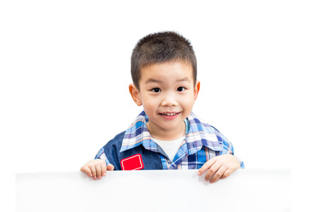 Portrait of happy little boy standing and holding empty white board isolated on white background