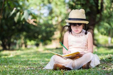 dessin enfants: Petite asiatique utilisation fille crayon �criture sur ordinateur portable pour �crire livre avec le visage souriant dans le parc Banque d'images