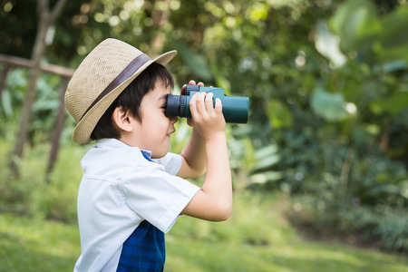 binoculars: Little asian boy looking trough a binoculars with smiling face in park