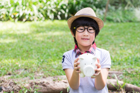 cradling: Little asian boy is holding his piggy bank in park