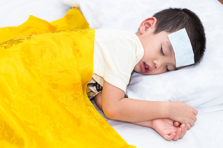 gels: Little asian boy has fever and sleep on bed with gels fever on head
