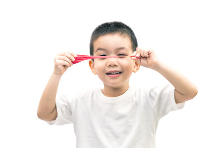 Little asian boy stretch a red balloon isolated on white background