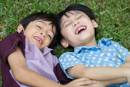 Two Little boy lay down on green grass and laugh