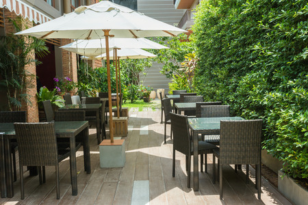 the place is outdoor: Cafe tables and chairs outside with big white umbrella and plant Stock Photo