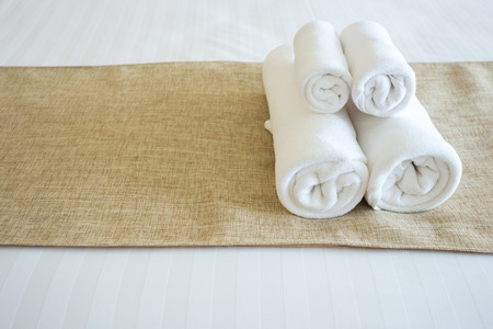 hotel stay: Close up of nice towels on white bed sheet with yellow ribbon