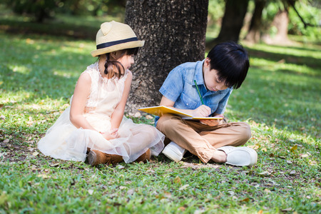 Little asian boy use pencil writting on notebook for writing book with smiling face in the park and younger sister looking at her brother Stock Photo
