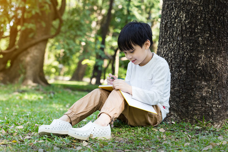 draws: Little asian boy sitting under the tree and drawing in notebook at park