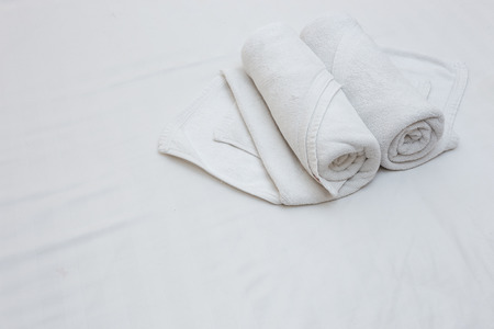 romance bed: Close up of nice white towels on white bed sheet Stock Photo