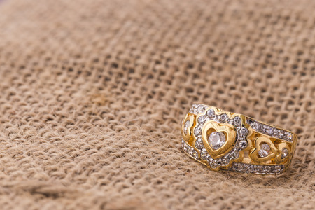 diamond shape: Heart shape diamond ring on burlap hessian sacking texture