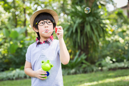 Asian little boy is blowing a soap bubbles with smile face in park Stok Fotoğraf