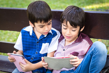 Little handsome boy looking on ipad tablet and playing game at park