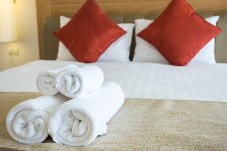 Close up of nice towels on white bed sheet with red pillow photo