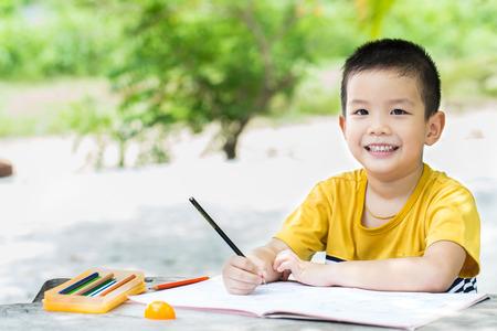 gar�on souriant: Petite asiatique �crit l'utilisation de gar�on de crayon sur ordinateur portable pour �crire livre avec un visage souriant sur la table en bois dans le parc