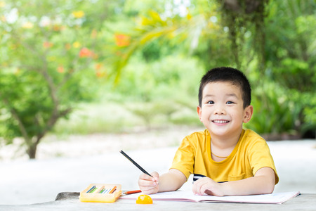 Little asian boy use pencil writing on notebook for writing book with smiling face on wooden table in the park Standard-Bild