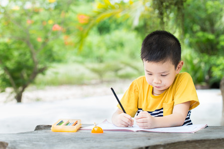 person writing: Little asian boy use pencil writing on notebook for writing book with smiling face on wooden table in the park Stock Photo