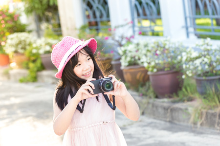 Little asian cute girl showing of camera and take a picture in park Standard-Bild