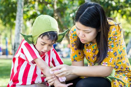 hemorragias: El niño pequeño brazo sangrante herida cerca del codo y de la madre ayudan a los primeros auxilios a él Foto de archivo