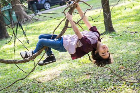 Little boy climb on a tree rope