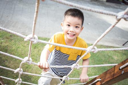 Weinig Aziatische jongen klimtouw obstakel activiteit op de speelplaats