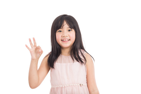 preteen model: beautiful little asian girl showing OK gesture isolated on white background
