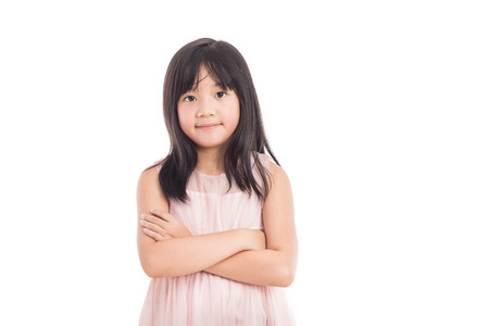 portrait of a little asian girl standing with folded hands over white background
