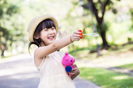 Asian little girl is blowing a soap bubbles with smile face in park