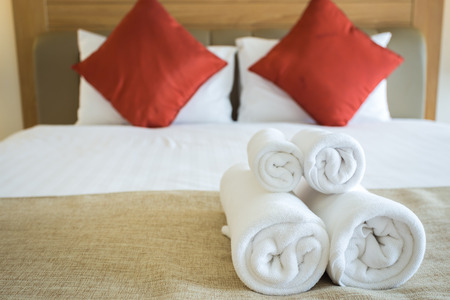 Close up of nice towels on white bed sheet with red pillow