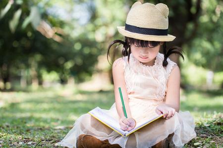 Weinig Aziatisch meisje gebruik potlood schriftelijke instructies op laptop voor het schrijven met een lachend gezicht in het park boek