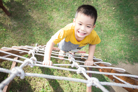 Little asian boy climbing rope obstacle activity on the playground