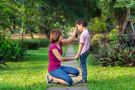Mother sitting at park holding hands and teaching her son Stock Photo