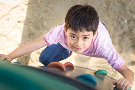 Little boy climbing up brave at playground Standard-Bild