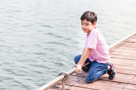 Little asian boy sit at waterfront