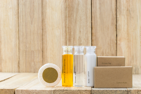 Tubes of bathroom amenity contains on wooden background