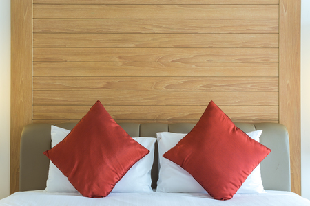Close up of red pillow on white bed sheet with wooden texture background