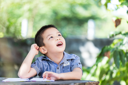 Little asian boy thinking and looks up for the future sit on wooden table in park