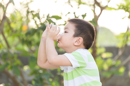 Little boy drinking milk in the park with sunshine in background